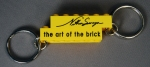 nathan sawaya the art of the brick keychain yellow with black text
